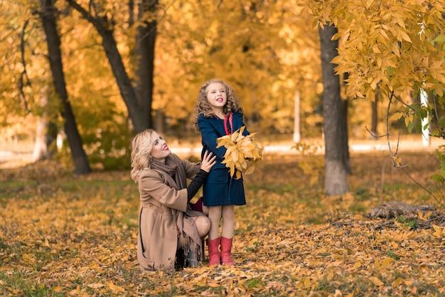 Feliz familia madre e hija hijo en otoño a pie