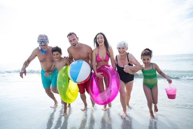 Feliz familia multigeneracional corriendo en la playa