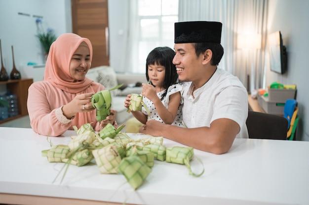 Feliz familia musulmana asiática haciendo ketupat juntos en casa antes del eid mubarak