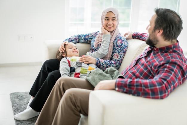 Feliz familia musulmana sentada en el sofá en living roome en casa