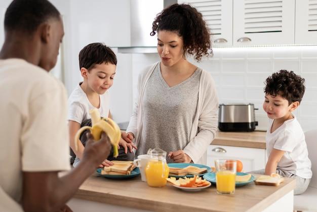 Feliz familia negra desayunando mientras sonríe