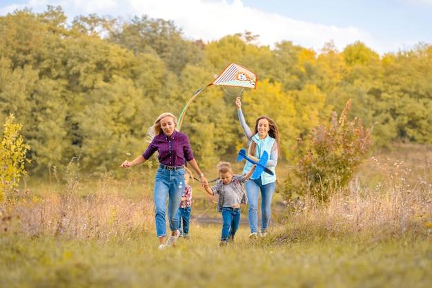 Feliz familia no tradicional de dos jóvenes madres y sus hijos lanzan una cometa sobre la naturaleza al atardecer