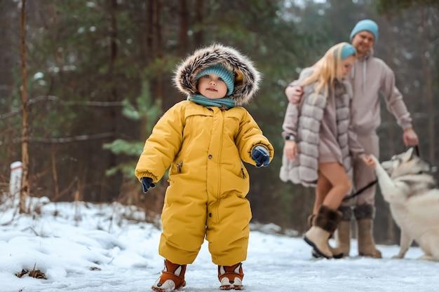 Feliz familia papá, mamá y bebé en un paseo de invierno en el bosque