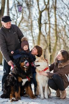 Feliz familia posa con divertido akita-inu y perro de montaña de bernese en la nieve