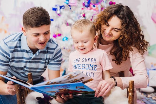 Feliz familia posa delante de un árbol de navidad en la habitación rosa