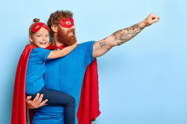 Feliz familia siendo líderes heroicos, use disfraces de superhéroe