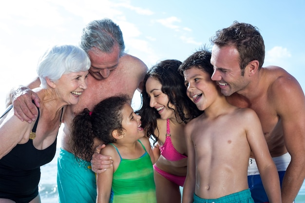 Feliz familia de varias generaciones de pie en la playa