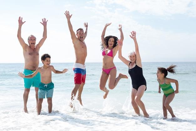 Feliz familia de varias generaciones saltando en la playa