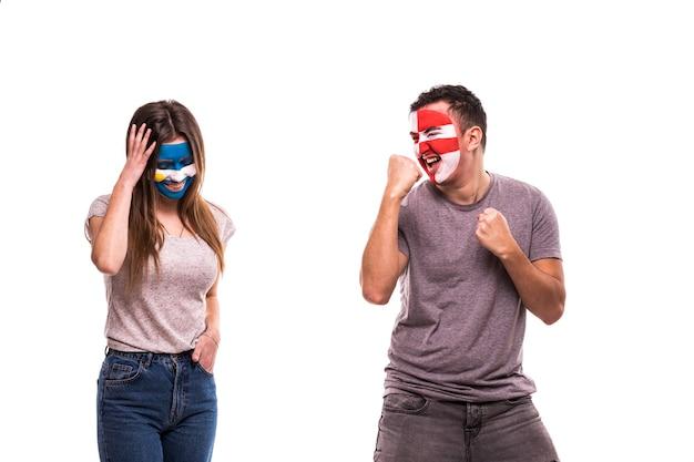 Feliz fanático del fútbol de croacia celebra la victoria sobre el molesto fanático del fútbol de argentina con la cara pintada