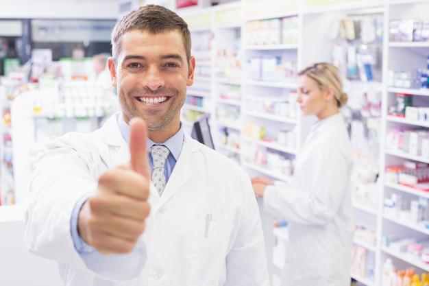 Feliz farmacéutico sosteniendo su pulgar