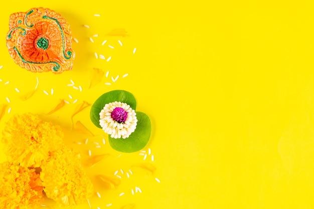 Feliz festival de dussehra. arcilla diya y flor sobre papel amarillo con texto. endecha plana