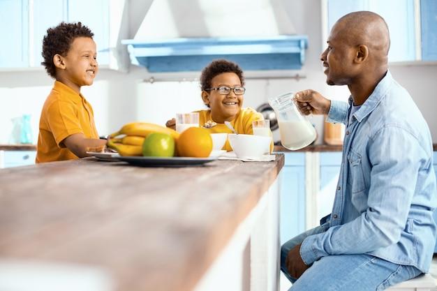 Feliz fin de semana. alegre monoparental sentado a la mesa y discutiendo el plan del día mientras desayuna en la cocina