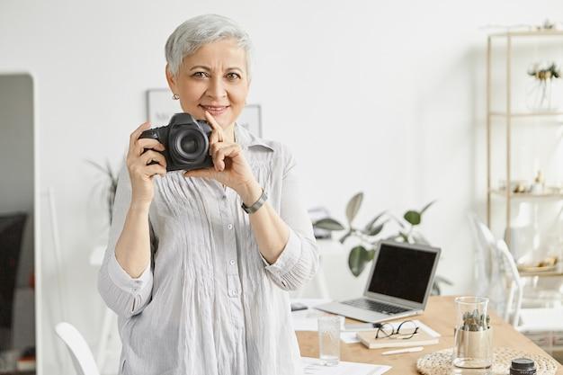 Feliz fotógrafa de mediana edad con pelo gris corto sosteniendo una cámara dslr profesional y sonriendo, posando en el elegante interior de la oficina