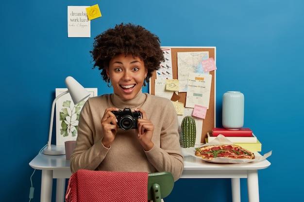 Feliz fotógrafa rizada confiada sostiene una cámara retro, feliz de pasar el tiempo libre en hobby, siendo una persona creativa