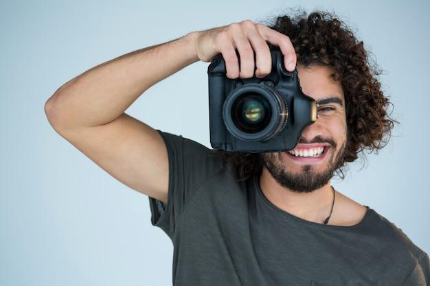 Feliz fotógrafo masculino con cámara digital en estudio