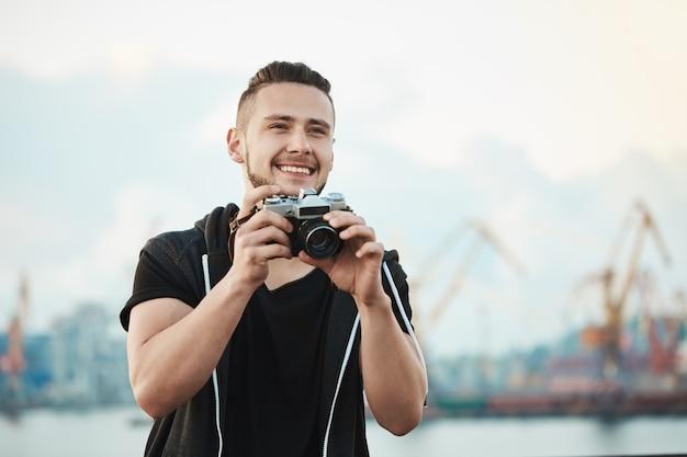 Feliz fotógrafo satisfecho sonriendo ampliamente mientras mira a un lado y sostiene la cámara