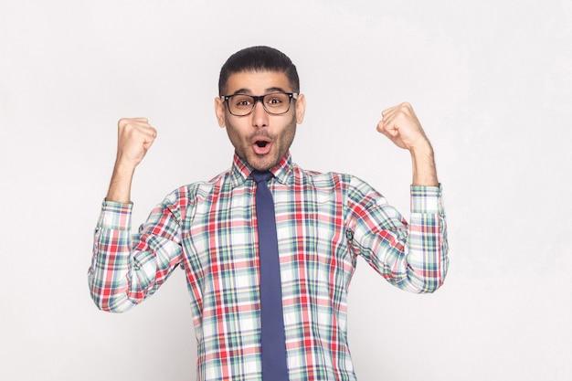 Feliz ganador guapo empresario barbudo en camisa a cuadros, corbata azul y anteojos negros de pie gritando y mirando a cámara con las manos levantadas. foto de estudio de interior, aislado sobre fondo gris