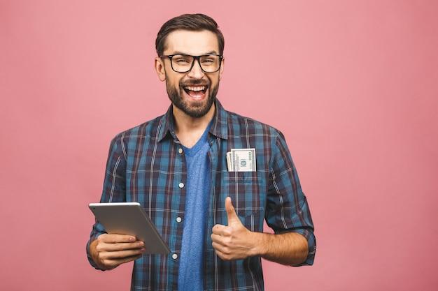 Feliz ganador! hombre rico joven en billetes de dólar que se sostienen casuales del dinero y tableta con la sorpresa aislada sobre la pared rosada. pulgares hacia arriba.