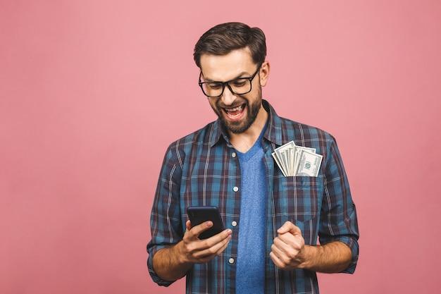 Feliz ganador! hombre rico joven en la camisa a cuadros que lleva a cabo billetes de dólar del dinero en el bolsillo con la sorpresa aislada sobre fondo rosado. usando el teléfono.