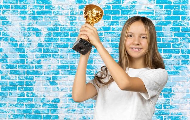 Feliz ganador, retrato de la hermosa teen girl student con trofeo de oro