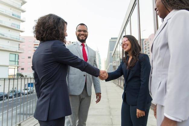 Feliz gerente mujer bienvenida socios fuera