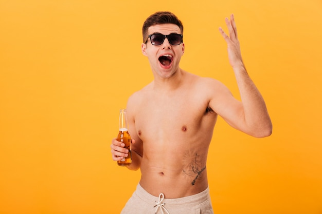 Feliz gritando hombre desnudo en pantalones cortos y gafas de sol con botella de cerveza sobre amarillo
