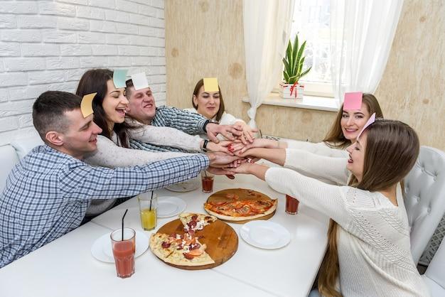 Feliz grupo de amigos en el café comiendo pizza