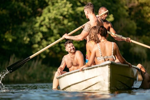 Feliz grupo de amigos divirtiéndose, riendo y nadando en el río
