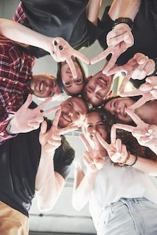 Feliz grupo de amigos con las manos juntas en el medio
