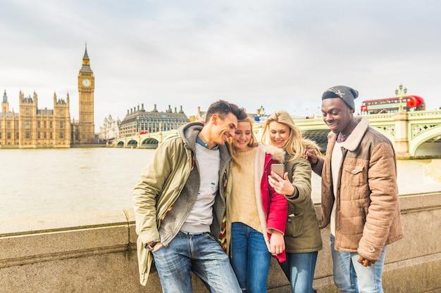 Feliz grupo de amigos multirraciales usando un teléfono inteligente en londres