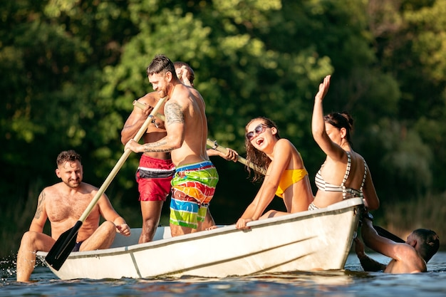 Feliz grupo de amigos que se divierten mientras se ríen y nadan en el río. hombres y mujeres alegres en traje de baño en un barco en la orilla del río en un día soleado. verano, amistad, resort, concepto de fin de semana.