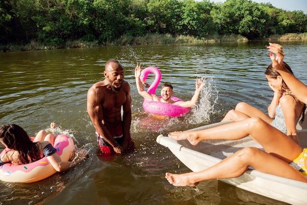 Feliz grupo de amigos que se divierten mientras se ríen y nadan en el río