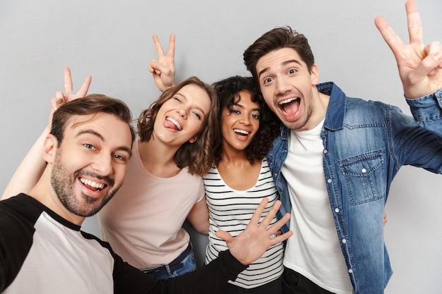 Feliz grupo de amigos que muestran gesto de paz hacen selfie.