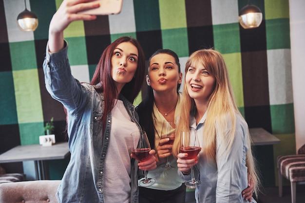 Feliz grupo de amigos con vino tinto tomando selfie