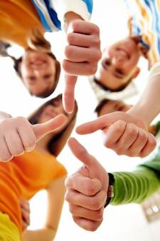 Feliz grupo de amigos con los pulgares arriba
