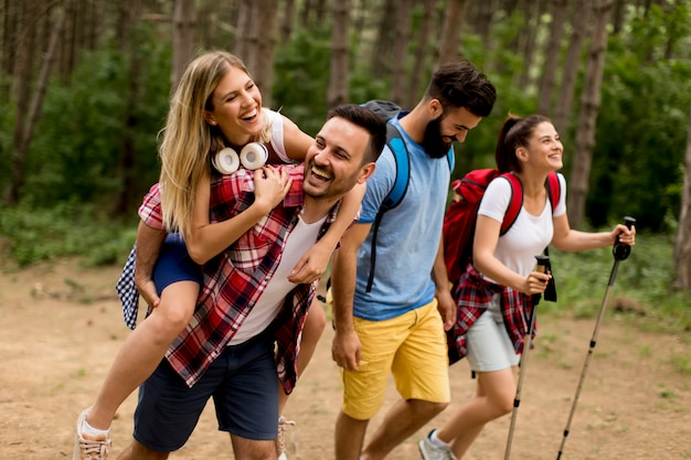 Feliz grupo joven caminando juntos por el bosque