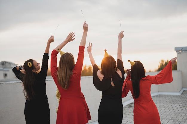 Feliz grupo de mujeres admirando la puesta de sol en la azotea