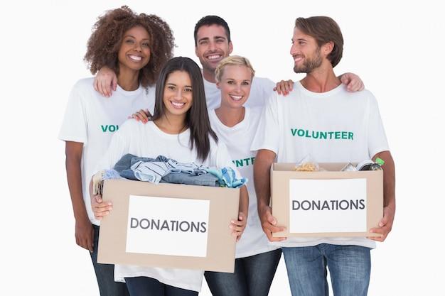 Feliz grupo de voluntarios con cajas de donación de ropa