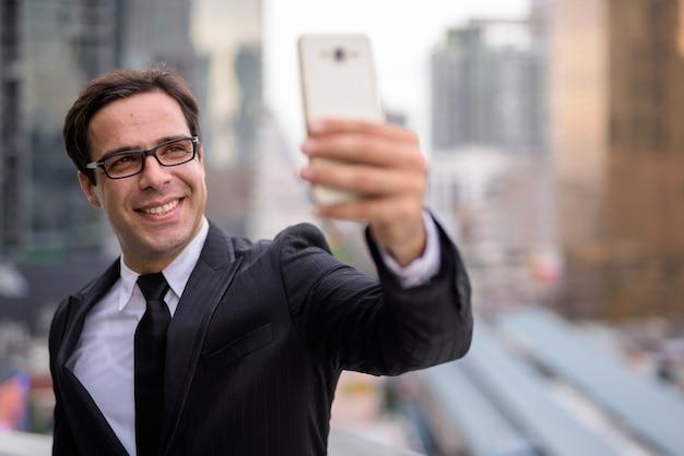 Feliz guapo empresario tomando selfie en la ciudad