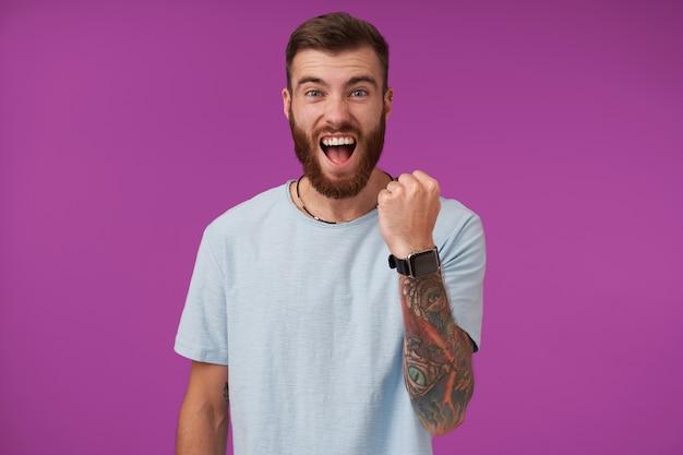 Feliz guapo joven morena tatuada con barba manteniendo el puño en alto y gritando alegremente mientras posa en púrpura en ropa casual