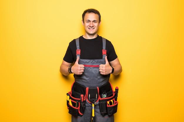Feliz guapo joven trabajador sonriendo y pulgares arriba, chico con ropa de trabajo y equipo de cinturón