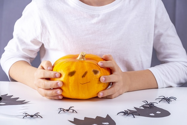 Feliz halloween. chico guapo con calabaza con cara divertida.