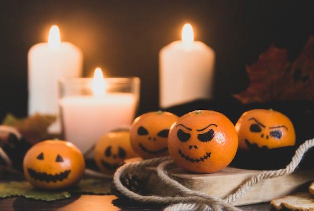 Feliz halloween cítricos, mandarinas pintadas con caras aterradoras y divertidas. foto oscura con velas. alternativas a las tradicionales calabazas de halloween.