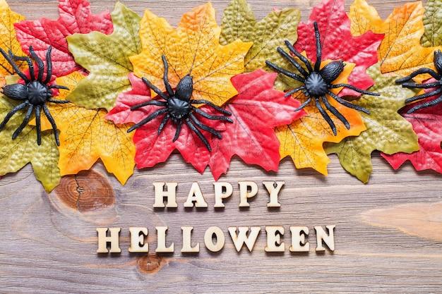 Feliz halloween. letras de frase rodeadas de hojas de arce y arañas en madera