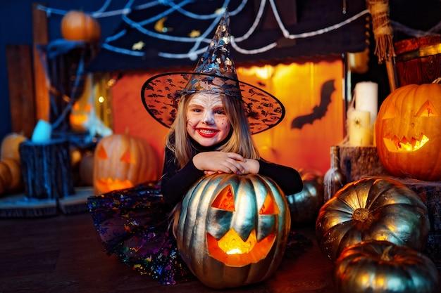 Feliz halloween. una niña hermosa en un disfraz de bruja celebra con calabazas