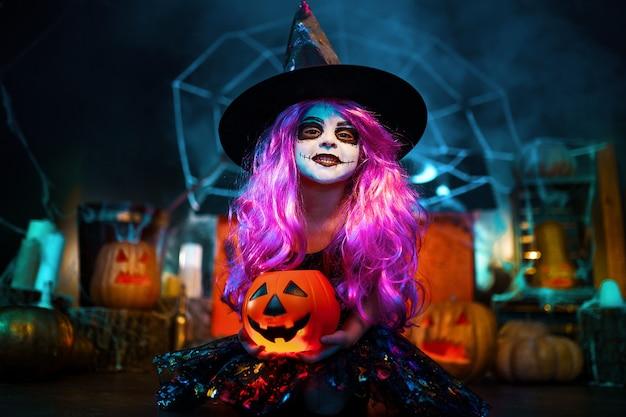 Feliz halloween. una niña hermosa en un disfraz de bruja celebra en casa en un interior con calabazas y casa mágica de cartón