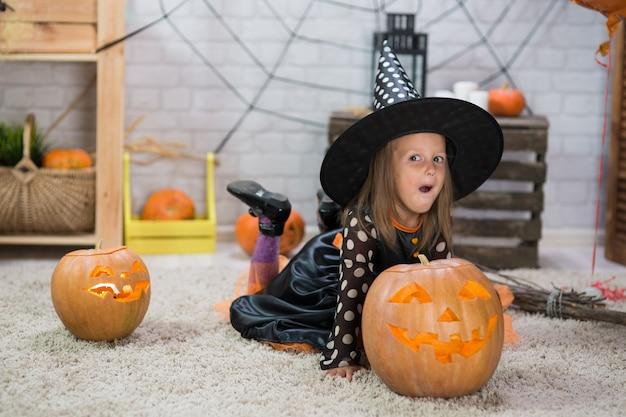 Feliz halloween. una niña hermosa en un disfraz de bruja celebra una casa en un interior con calabazas
