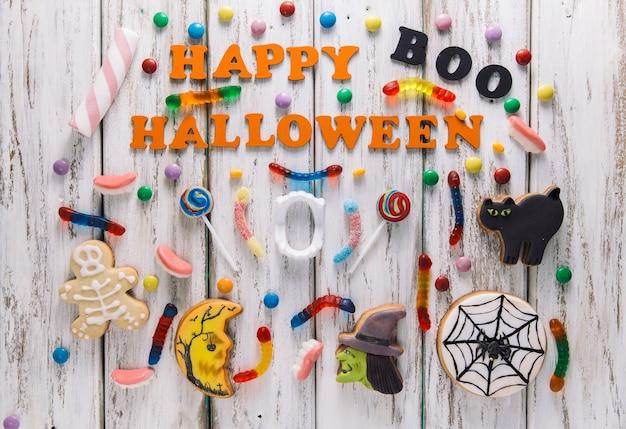 Feliz halloween subtítulo con dulces y galletas