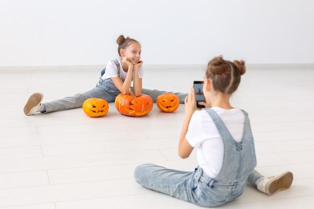 Feliz halloween, vacaciones y concepto de infancia: lindas hermanas gemelas niñas con calabazas jack-o'-lantern divirtiéndose mientras pasan tiempo en el interior.