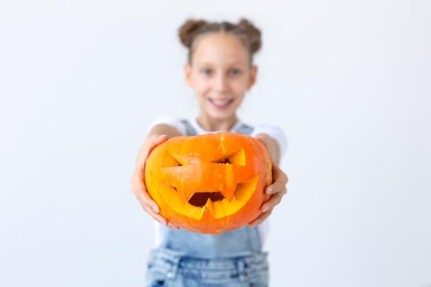 Feliz halloween, vacaciones de otoño y concepto de infancia - niña linda con un primer plano de calabaza jack-o'-lantern